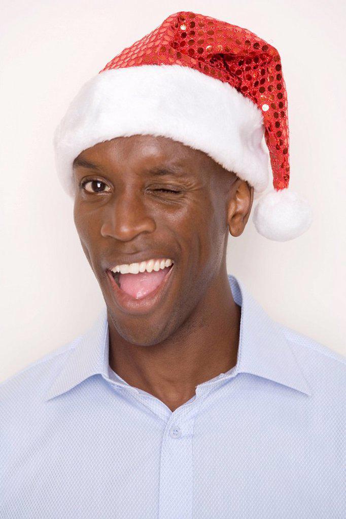 Man wearing Christmas hat, winking. : Stock Photo