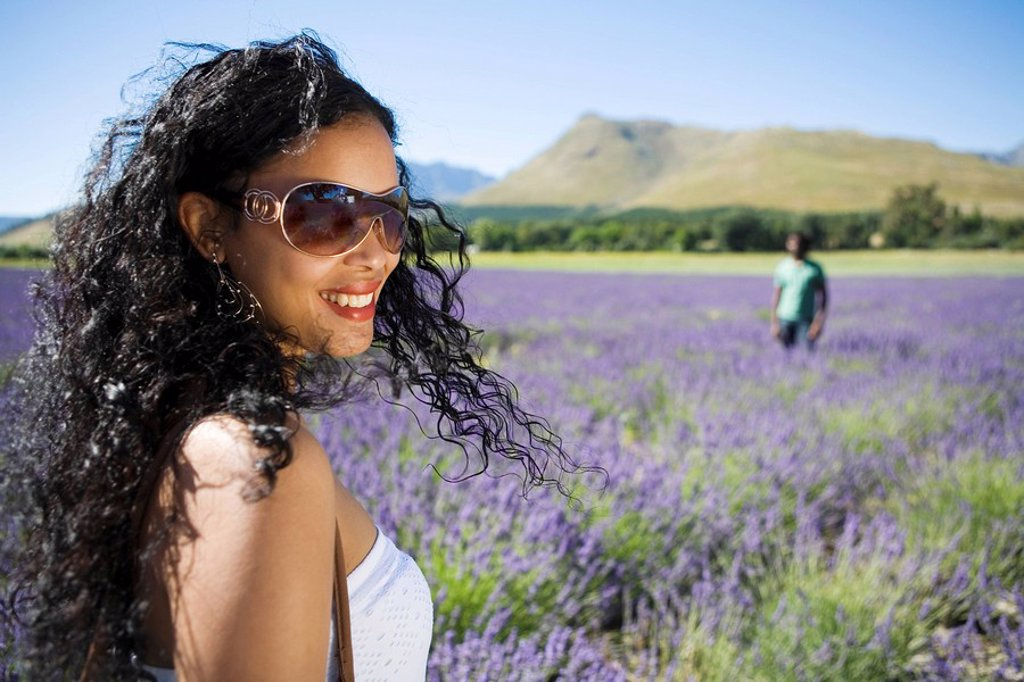 Close up view of woman standing in lavender field with man in background, Franschhoek, Western Cape Province, South Africa : Stock Photo