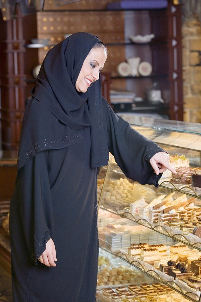 Smiling Arab Woman Pointing at Desserts in Bakery Display Window, Side View  Dubai, United Arab Emirates : Stock Photo
