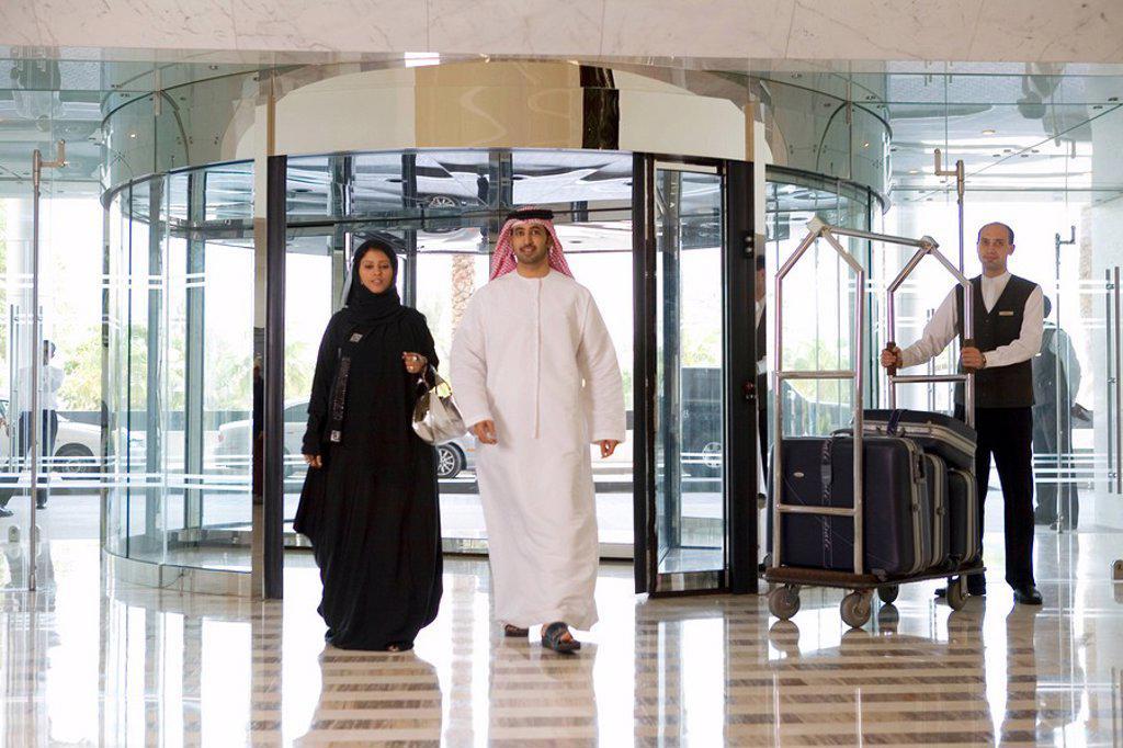 Stock Photo: 1896R-4922 Arab Couple Entering Hotel Lobby  Dubai, United Arab Emirates