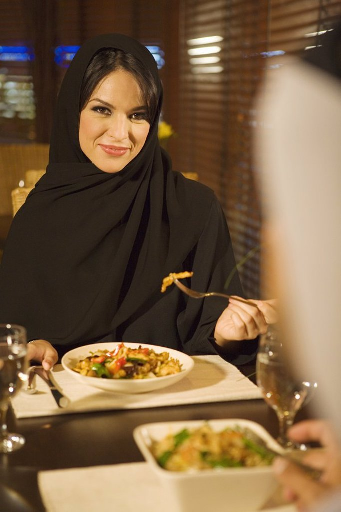 Stock Photo: 1896R-5070 Arab woman dining with husband in restaurant  United Arab Emirates