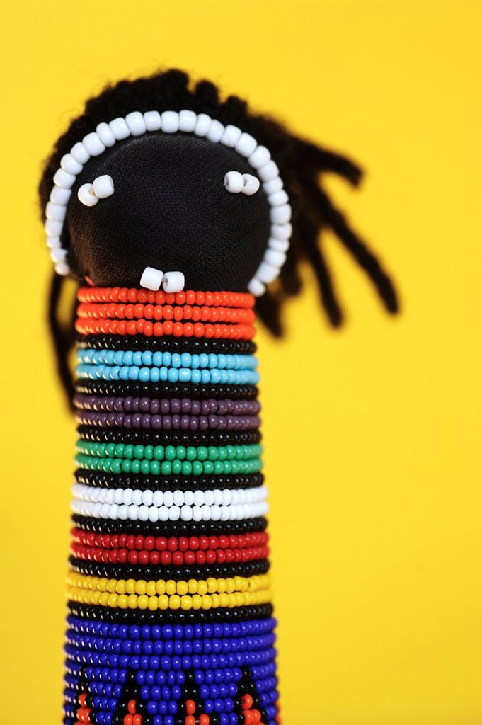 A Hand Made African Ndebele Doll Against a Yellow Background  Studio Shot : Stock Photo