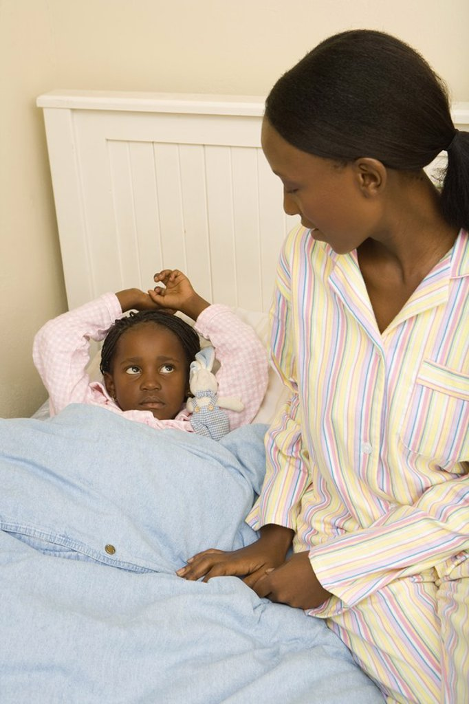African Woman Tucking her Daughter into Bed  Cape Town, Western Cape Province, South Africa : Stock Photo