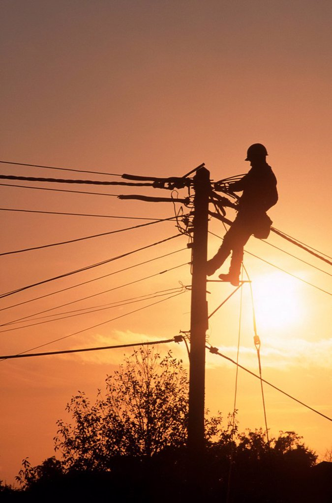 Silhouette of a Man Working on a Telegraph Pole at Sunset  England, United Kingdom : Stock Photo