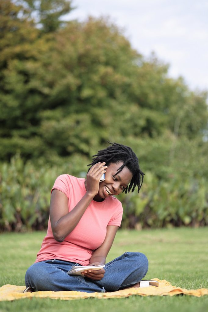 Young Woman Sitting Cross Legged on the Grass Talking on her Cellphone  Grahamstown, Eastern Cape Province, South Africa : Stock Photo
