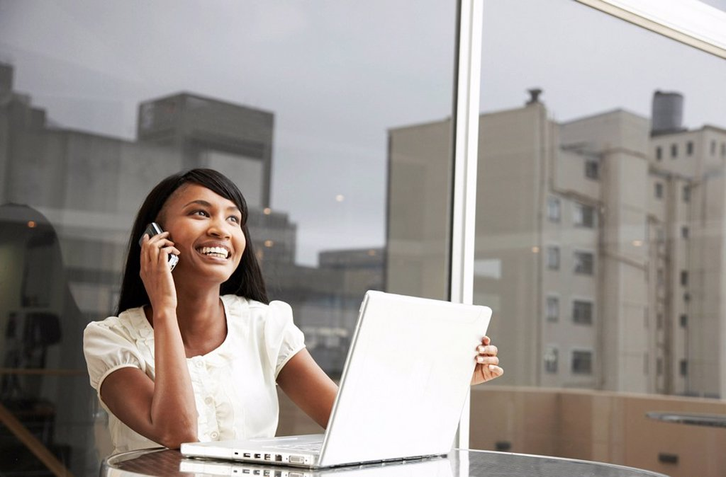 Stock Photo: 1896R-6091 Businesswoman using mobile phone in office environment, Cape Town, Western Cape Province, South Africa