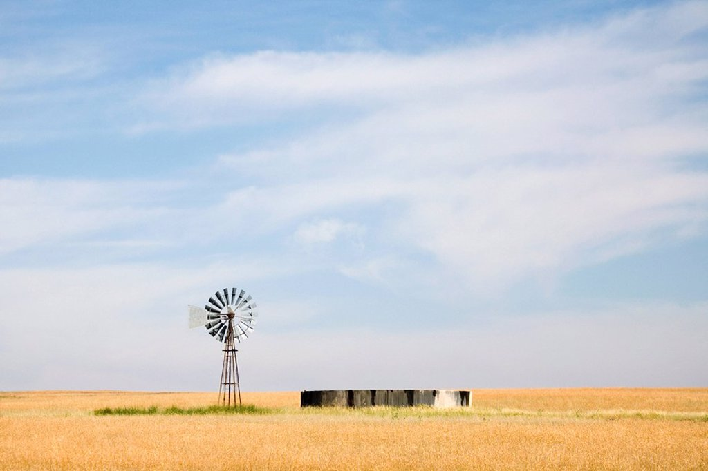 Stock Photo: 1896R-6381 The vastness of a Free State Province farm, with typical windmill and dam in the grasslands. South Africa