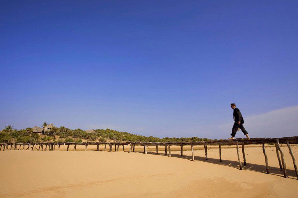 Businessman on raised boardwalk above beach, Lamu Island, Kenya : Stock Photo