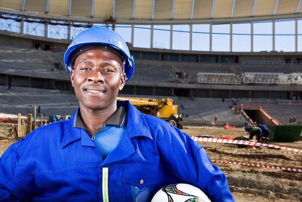 Construction worker with fooballand in front of construction work, Moses Mabhida Stadium, Durban, KwaZului_Natal Province, South Africa : Stock Photo