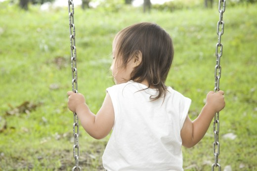 Stock Photo: 1897R-10797 Girl sitting on swing