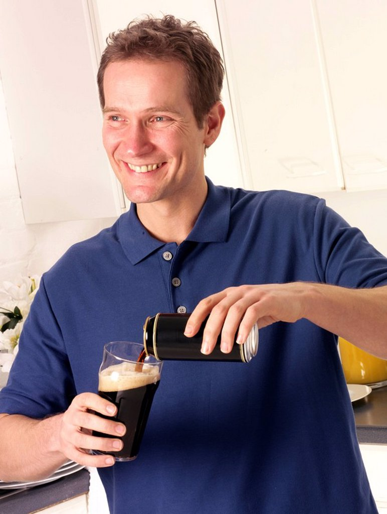 Stock Photo: 1898-13708 Man In Kitchen Pouring Guinness Or Dry Stout Ale