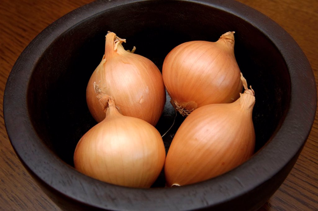 Onions in black bowl : Stock Photo