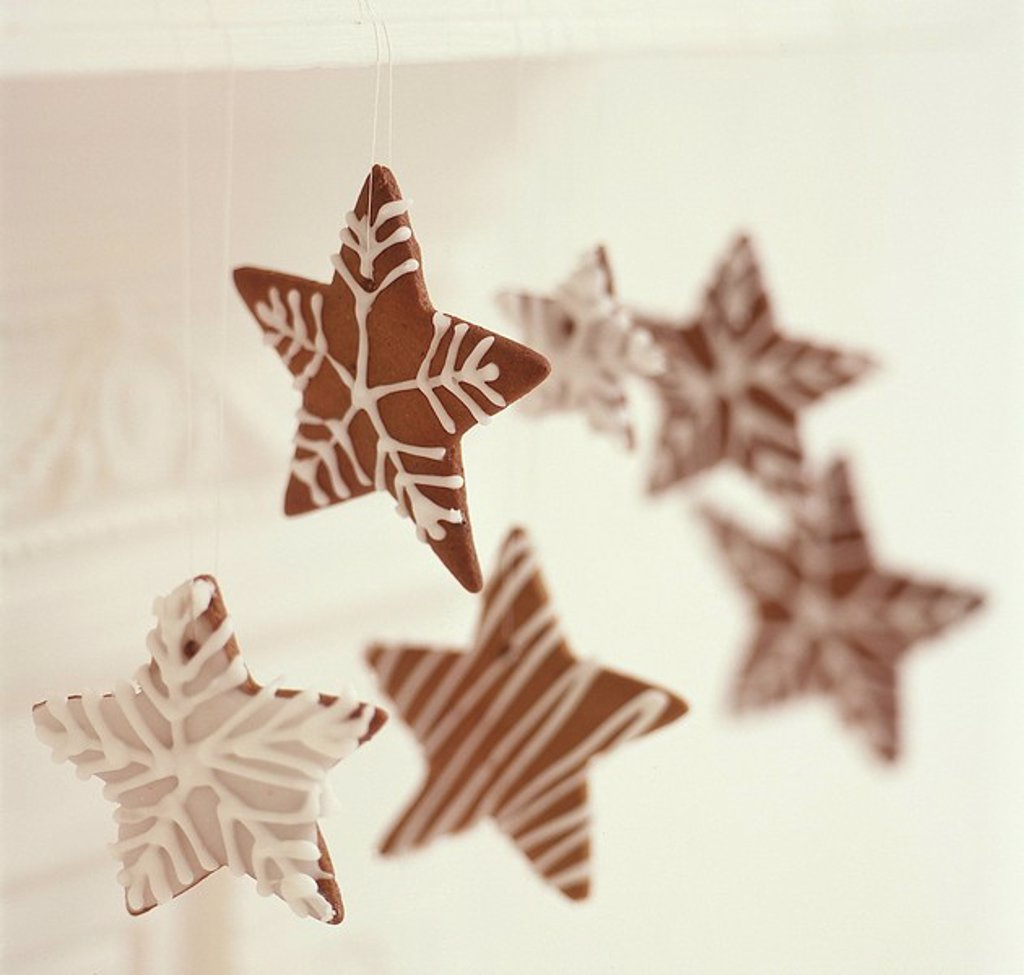 Stock Photo: 1898-28706 Homemade, star shaped cookies hanging from white mantle piece.