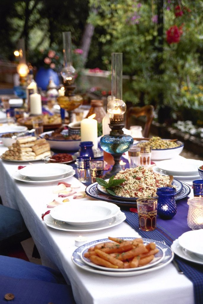 An outdoor dining table set for dinner with blue and white dinnerware, plates of food, and lit lanterns. : Stock Photo