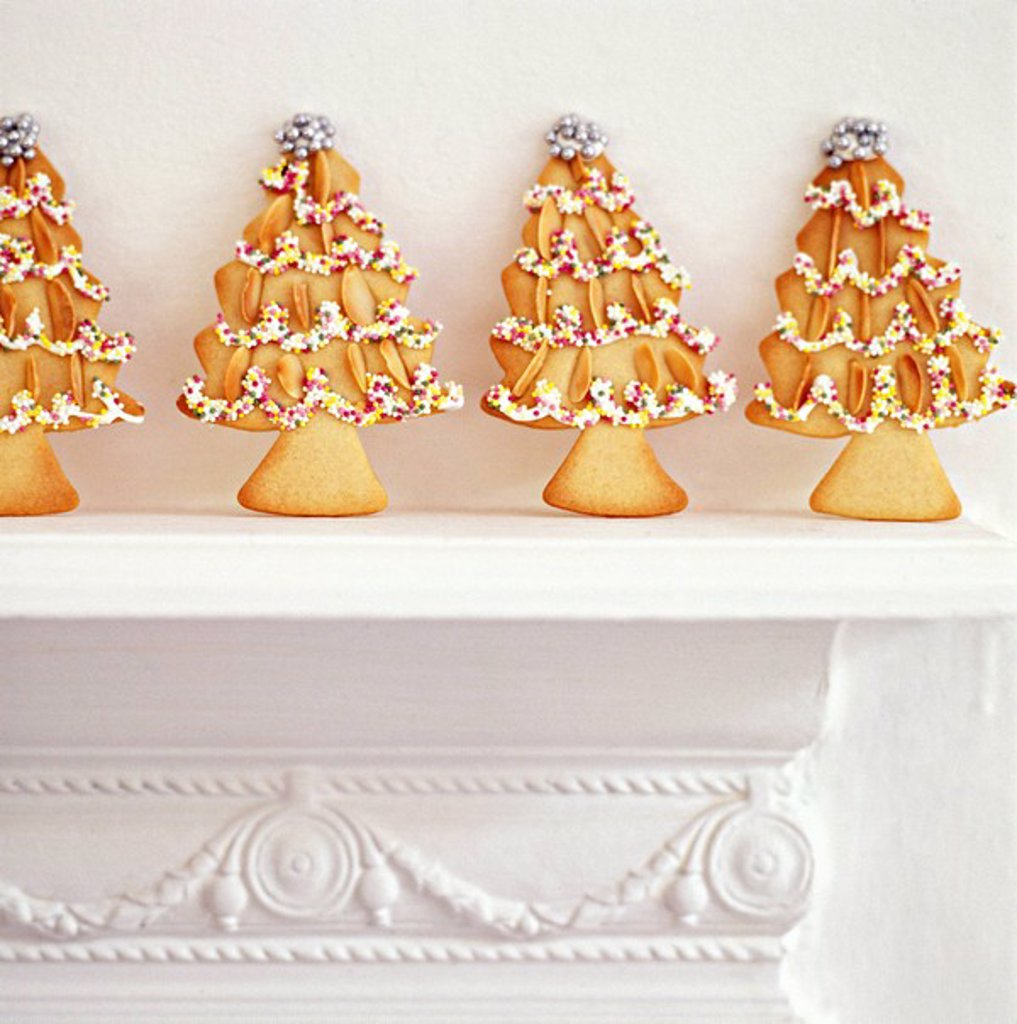 Stock Photo: 1898-28796 Baked, decorative Christmas tree cookies in a row upon a mantle.