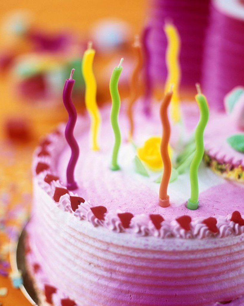 Close up details of a colourful birthday cake with colourful wavy candles. : Stock Photo