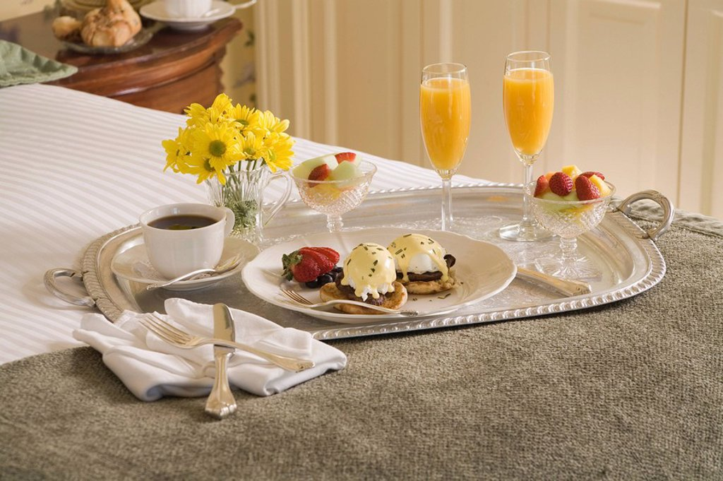 Eggs benedict and orange juice on silver tray on bed : Stock Photo