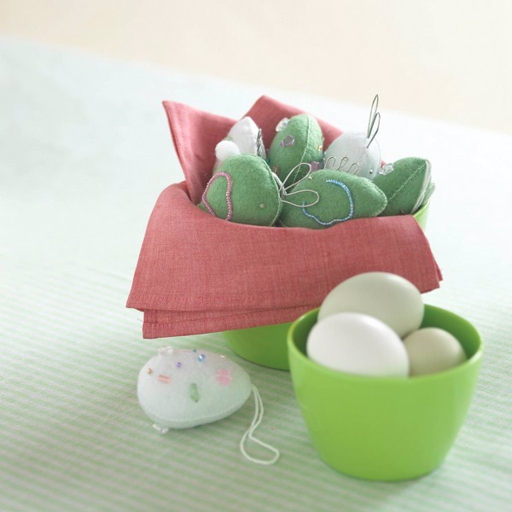 Embroidered ornaments and eggs in green bowls : Stock Photo