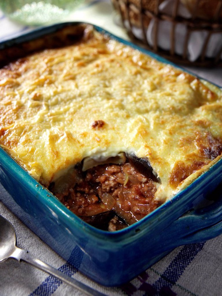 A whole moussaka in its baking dish a single serving taken out editorial food : Stock Photo