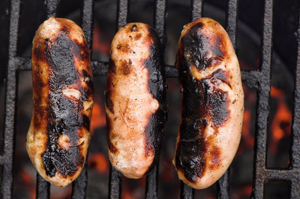 Sausages cooking on barbeque : Stock Photo