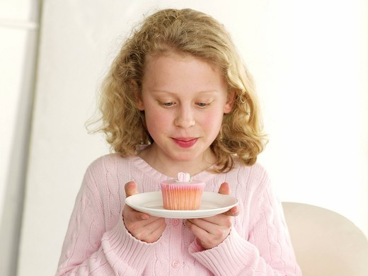 Stock Photo: 1898-46469 Young girl with pink Fairy cake  Model release all media