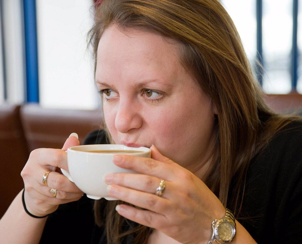 Woman drinking coffee in a cafe : Stock Photo