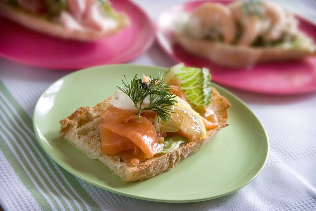 Rustic toasted bread topped with smoked salmon, aioli, capers, lemon and dill : Stock Photo