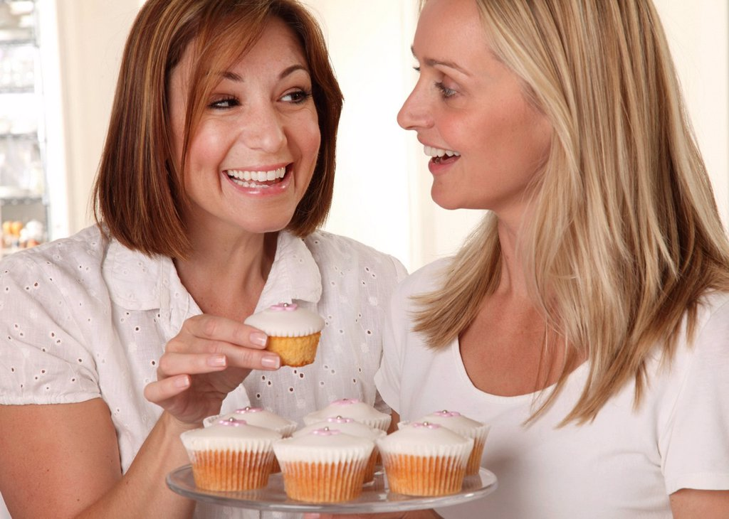 Stock Photo: 1898-51546 Two Women Eating Cupcakes