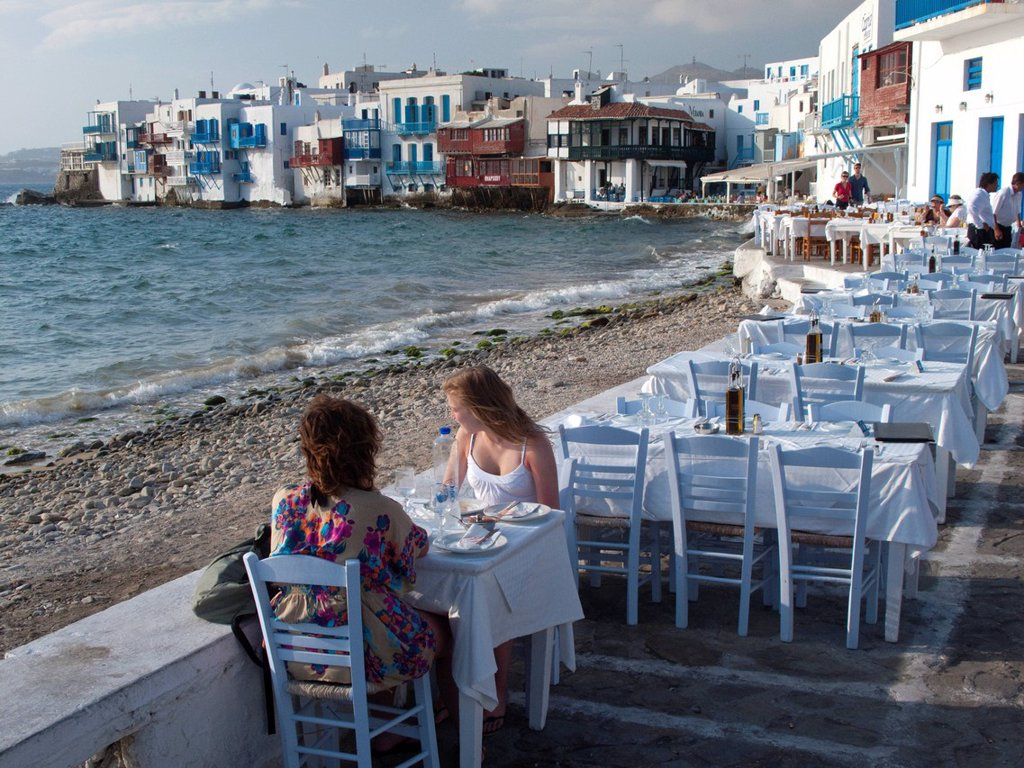 Two young women enjoying the view from an al fresco restaurant on the Greek Island of Mykonos, Greece : Stock Photo
