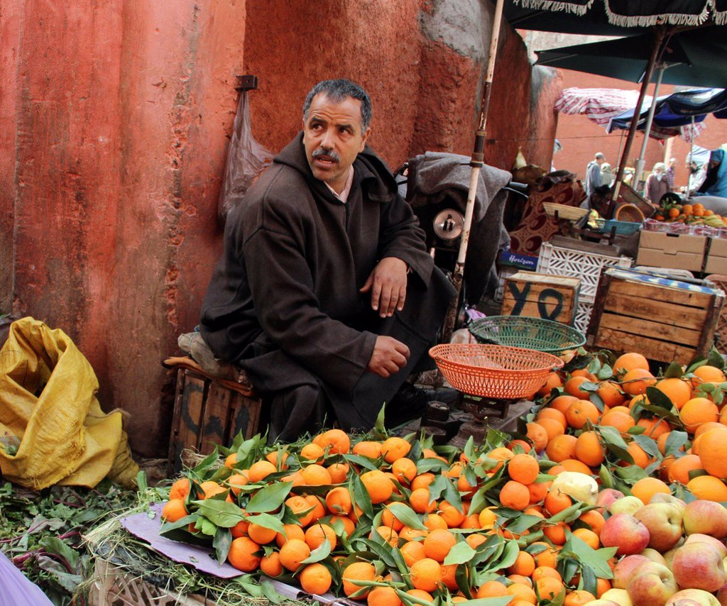 Moroccan market trader with fresh fruit on display : Stock Photo