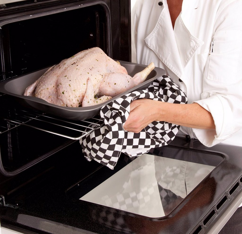 Stock Photo: 1898-53201 Chef putting chicken into an oven