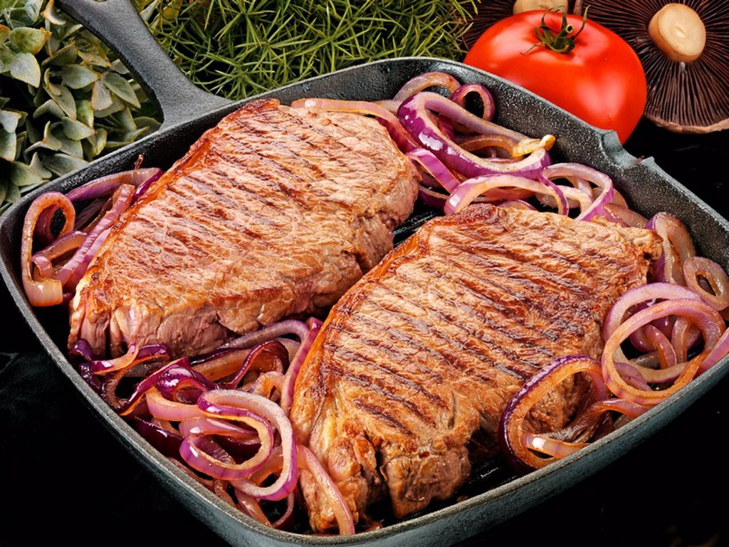 TWO SIRLOIN STEAKS WITH ONIONS : Stock Photo