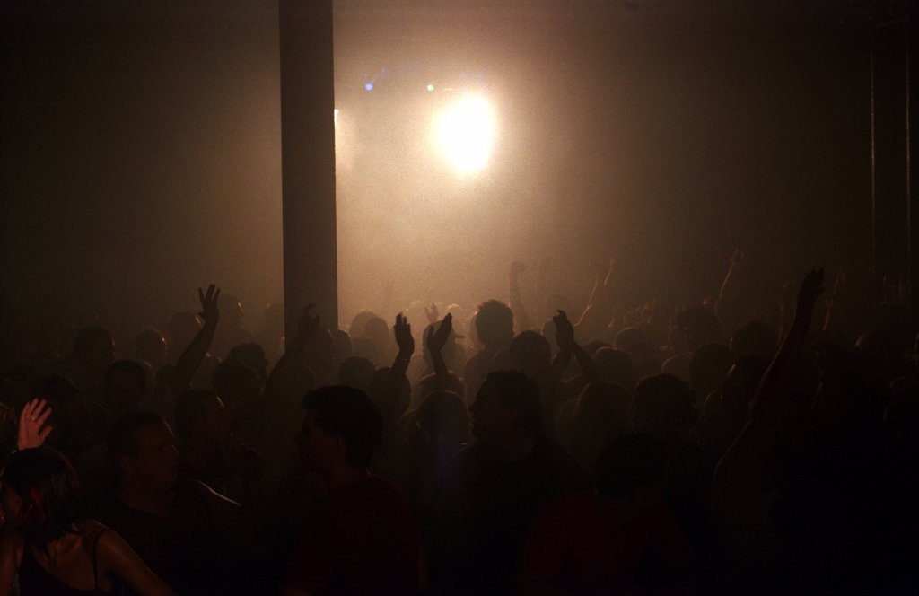 Silhouetted crowd and light at the Tribal Gathering Warehouse Party, Manchester, UK, August 2003.  : Stock Photo