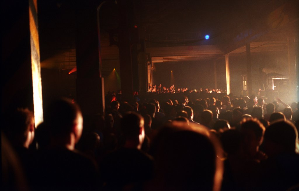 Silhouetted crowd watching the stage at Tribal Gathering Warehouse Party, Manchester, UK, August 2003.  : Stock Photo