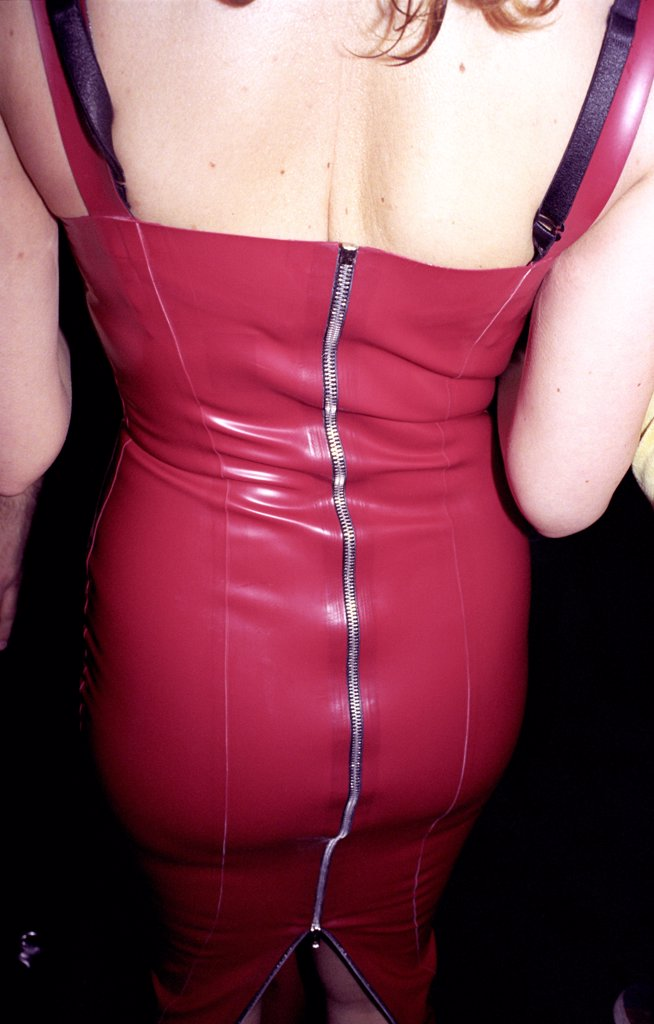 Woman in red pvc skirt with zip riding up the back, UK 2000s.  : Stock Photo