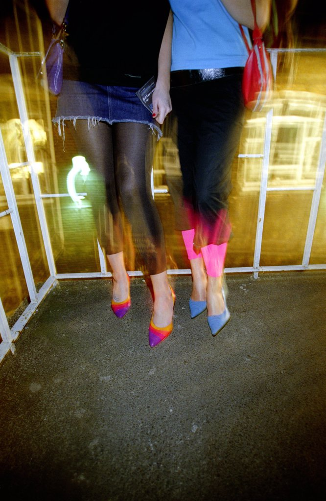 Close-up of girls legs, wearing a mini skirt, leggings and stileto shoes, at 93 Feet East, London, 2004.  : Stock Photo
