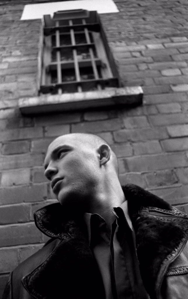 Youth leaning against a wall in a leather jacket, London 2002, MODEL RELEASED.  : Stock Photo