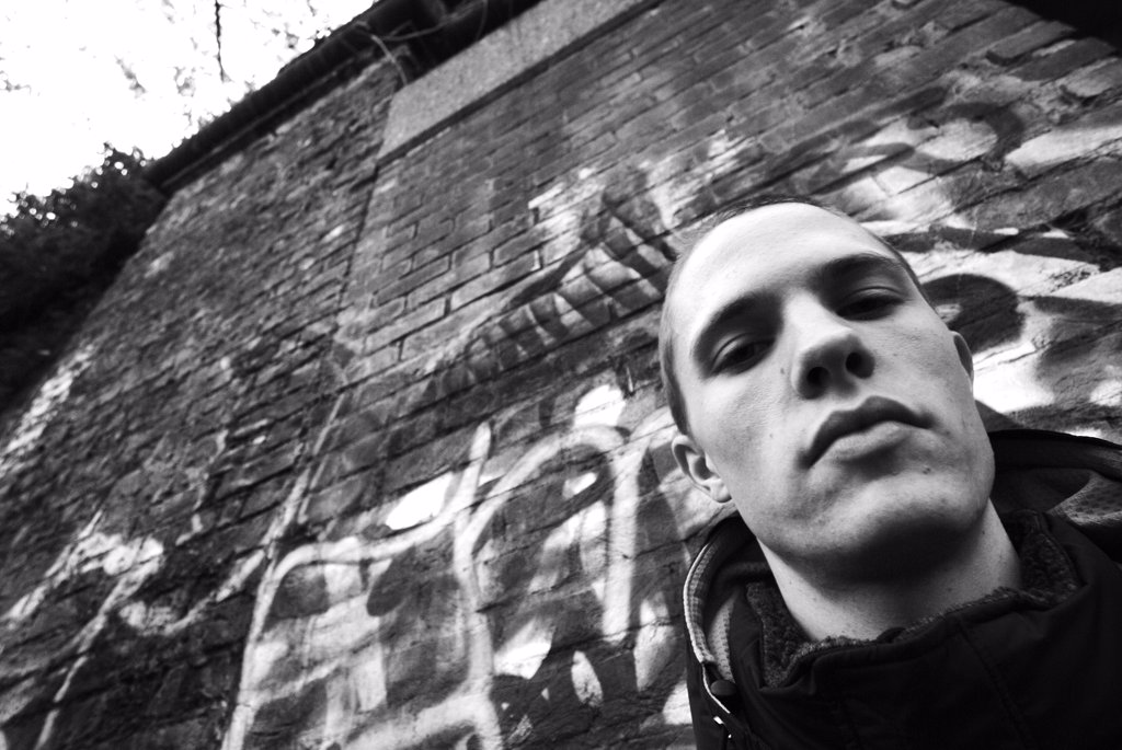 Stock Photo: 1899-13570 A young man wearing a hoodie, Stood by Graffiti, UK 2005.