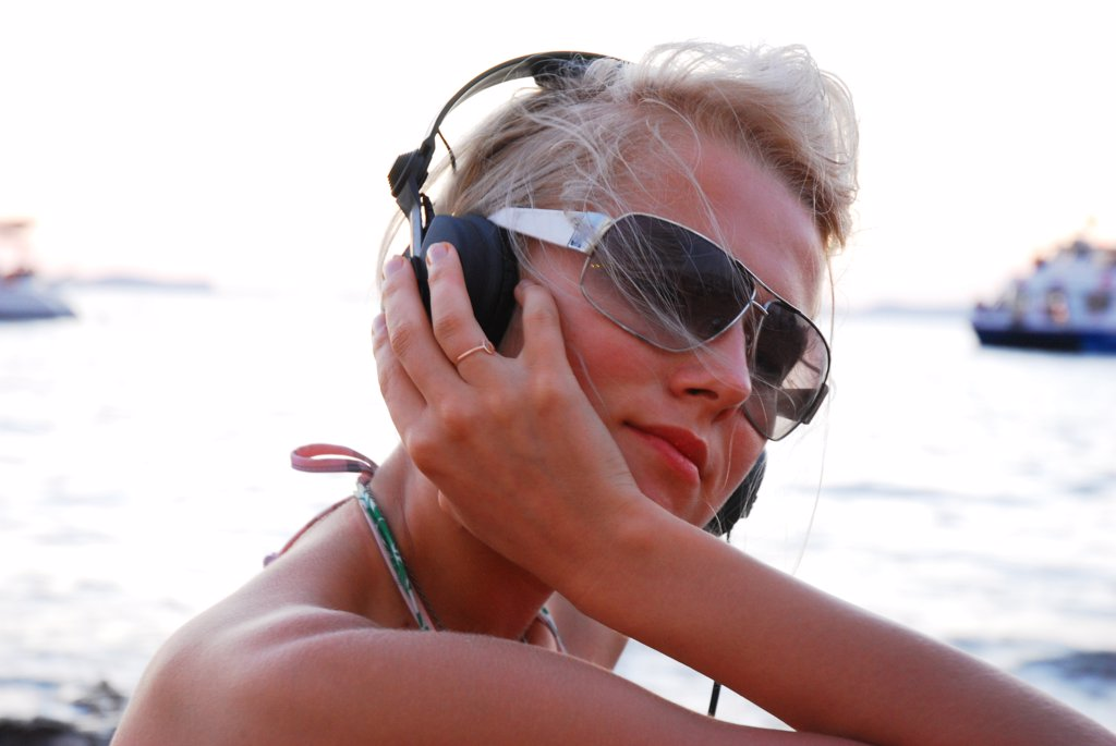 A sexy young girl listening to music on headphones, at sunset, Ibiza, 2006.  : Stock Photo