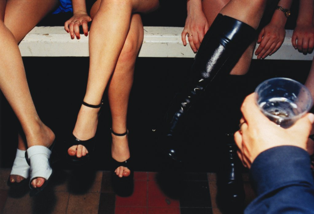 Women's Legs in Assorted Shoes and Hand Holding Drink.  : Stock Photo