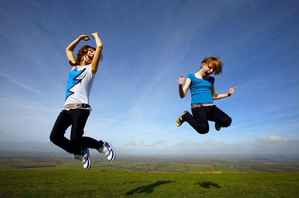 Stock Photo: 1899-13744 Two young girls leaping into the air in a field.