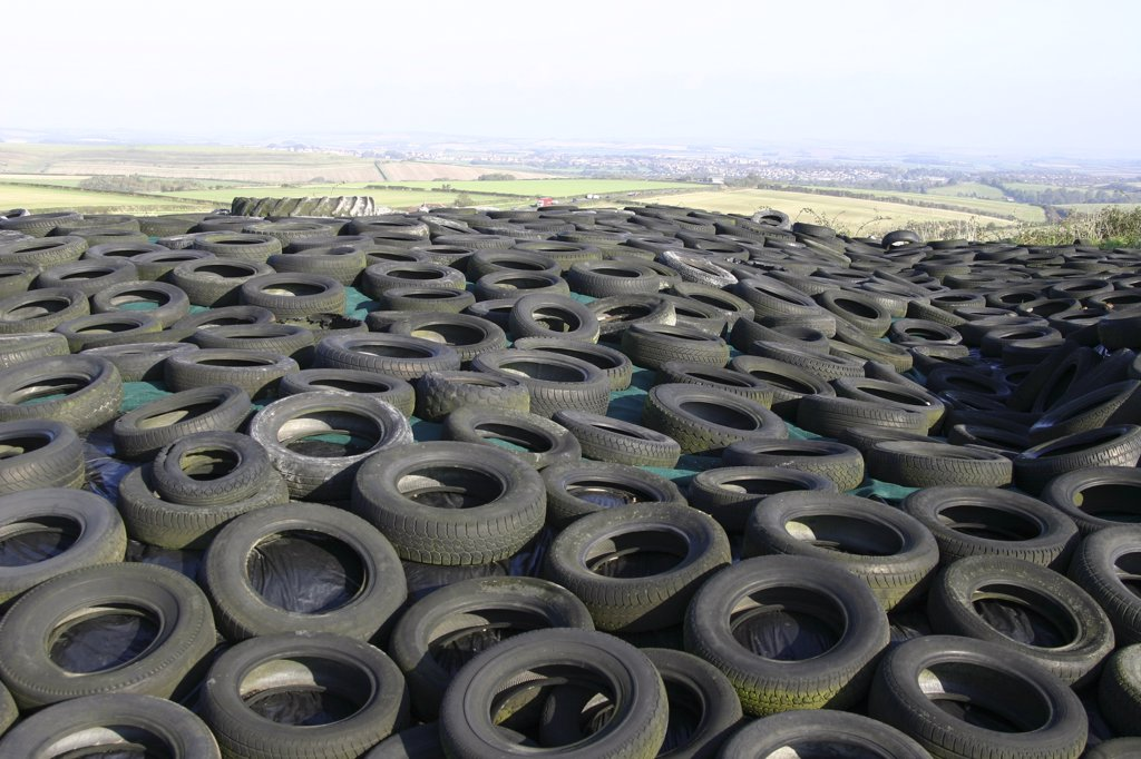 Stock Photo: 1899-21311 Sea of rubber tyres in Dorset, United Kingdom. Old tyres cover a silage clamp near Dorchester Dorset. View of countryside behind.