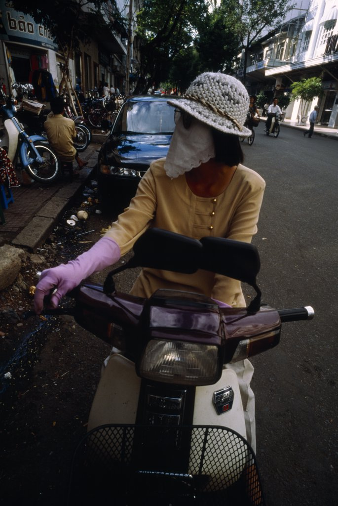 Stock Photo: 1899-21768 VIETNAM, Ho Chi Minh City. Woman on moped wearing a scarf over her nose and mouth to protect against the smog..