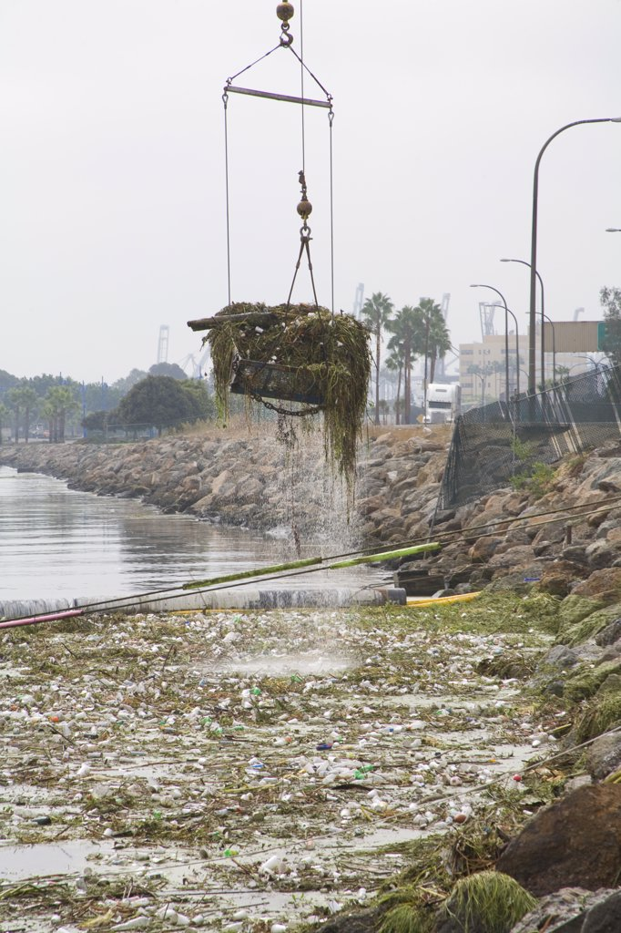 Stock Photo: 1899-24428 Los Angeles River garbage boom. Cranes picking up garbage debris after first rain of the season. The Garbage boom on the Los Angeles River in Long Beach was built in 2001. Urban runoff carries an assortment of trash and debris from catch basins where a network of pipes and open channels create a pathway to the Ocean. The man made debris can include plastic bags and bottles, Styrofoam cups, cans, tires, and household furniture. After the first major storm of the season, the boom may collect over