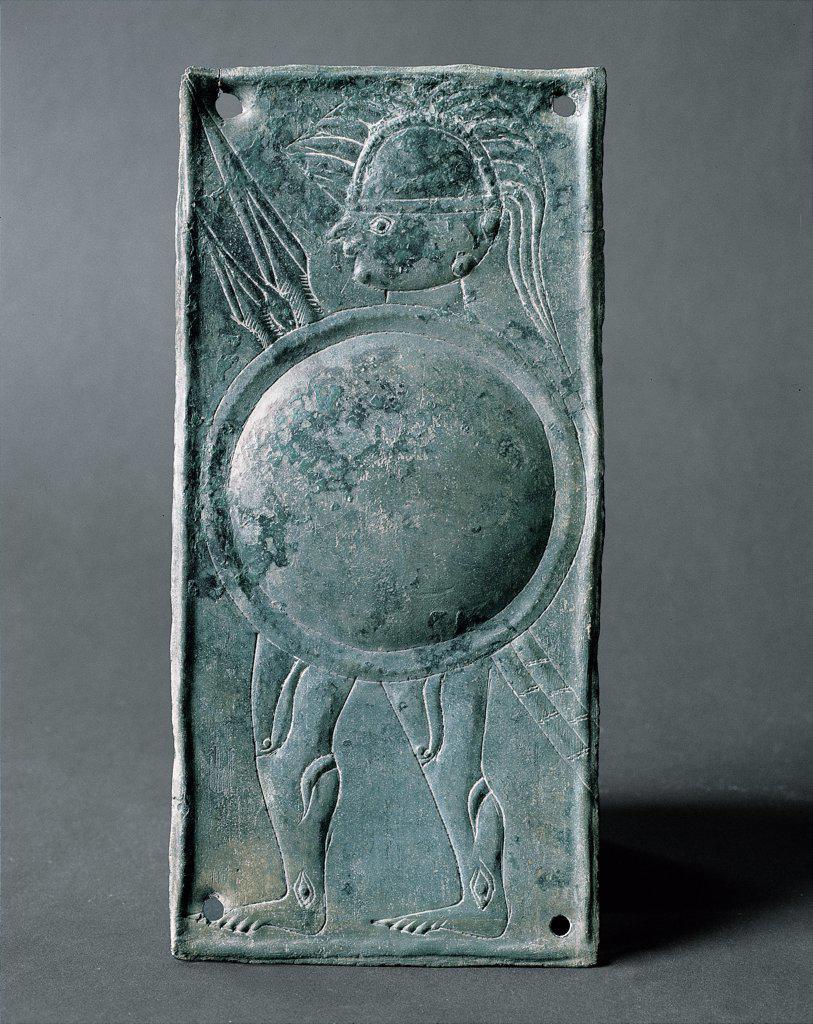 Warrior with round shield - Caldevigo, by Unknown, 5th Century, bronze. Italy, Veneto, Este, National Museum. Whole artwork. Lamina votive bronze warrior soldier lance: spear shield helmet cuirass jamb embossing. : Stock Photo