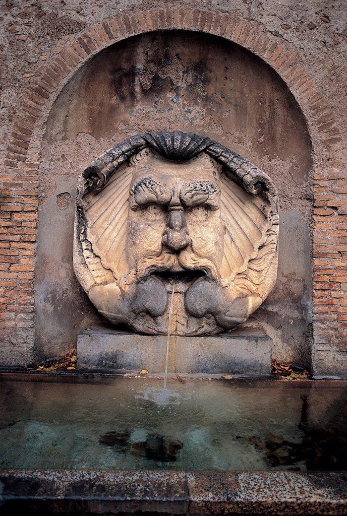 Fountain Mascherone of Santa Sabina, by Munoz (Munoz) Antonio, 1936, 20th Century, Unknow. Italy, Lazio, Rome, Piazza Pietro d'Illiria. Detail Mascherone fountain face valve jet shell niche water. : Stock Photo