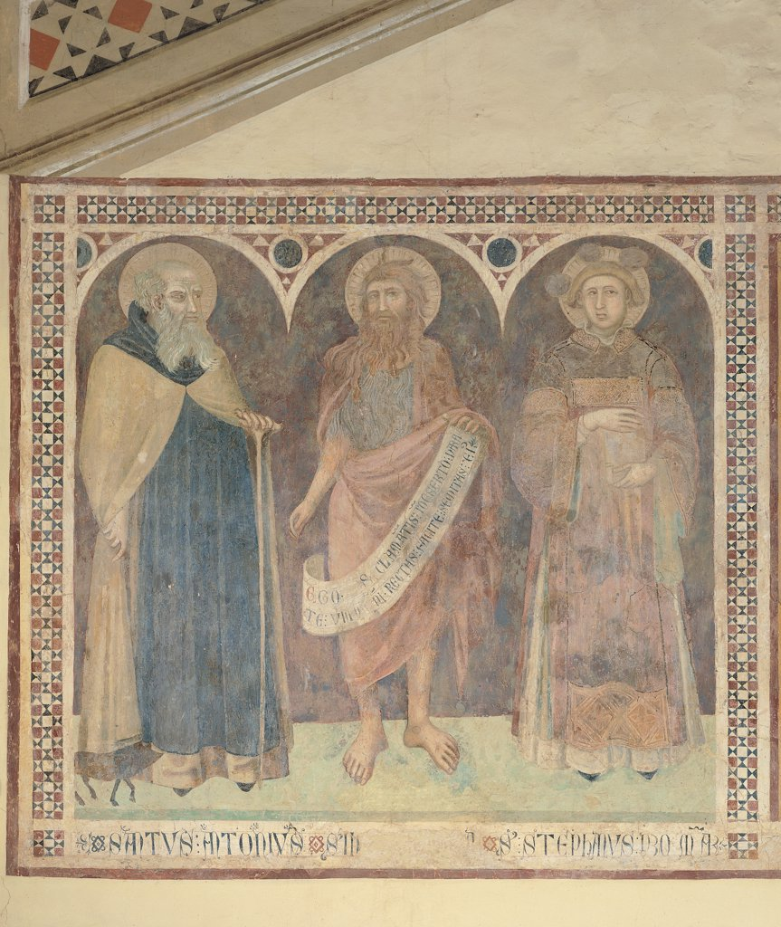 St Anthony the Abbot, St John the Baptist and St Stephen, by Lorenzetti Pietro, 1345, 14th Century, fresco. Italy, Tuscany, Castiglione del Bosco, Montalcino, Siena, San Michele Chapel. Whole artwork. Saints inscription geometric decoration St John the Baptist St Anthony the Abbot St Stephen round arch center blue yellow brown hues: shades halos: aureoles cartouche. : Stock Photo