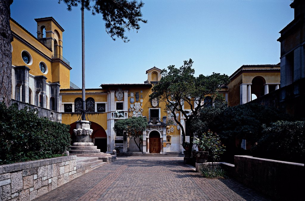 Stock Photo: 1899-32446 Vittoriale of Piazza Dalmata and 'La Priora' (D'Annunzio's House), by Unknown, 1921 - 1923, 20th Century, Unknow. Italy, Lombardy, Gardone Riviera, Brescia, The Vittoriale. View Piazzetta Dalmata La Prioria courtyard flower-beds trees.