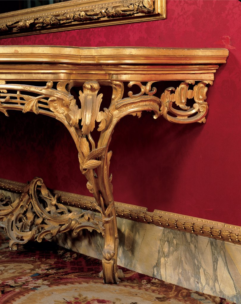 Console Table, by Emilian workmanship, 18th Century, wood carved and gilded, top covered with velvet. Italy, Tuscany, Florence, Palazzo Pitti, Quartiere d'Inverno. Detail. Wall table console gold rinceaux volutes red wall leaves. : Stock Photo