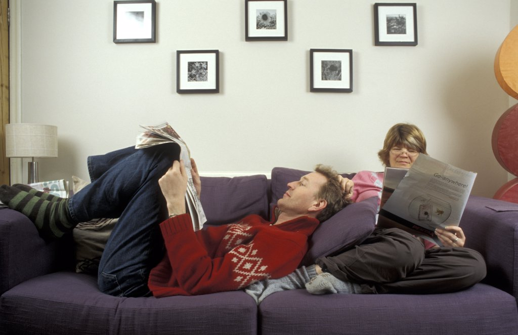 Couple reading weekend newspapers at home UK.  : Stock Photo